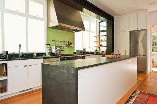 A Single Piece Green Glass Backsplash Livens Up This Warm Neutral Kitchen