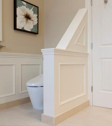 An image of a modern toilet niche, hidden from the rest of the bathroom by an angled half wall.