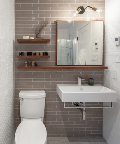 Long reclaimed wood shelves can help draw the eye from one part of the bathroom to the next, and can help balance out a bare wall (by Wanda Ely Architect Inc.)