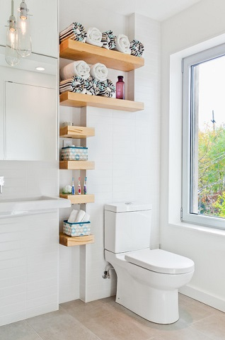 Thick, distinctive reclaimed wood shelves make a simple yet bold statement piece, especially set against an all white backdrop (by Wanda Ely Architect Inc.)