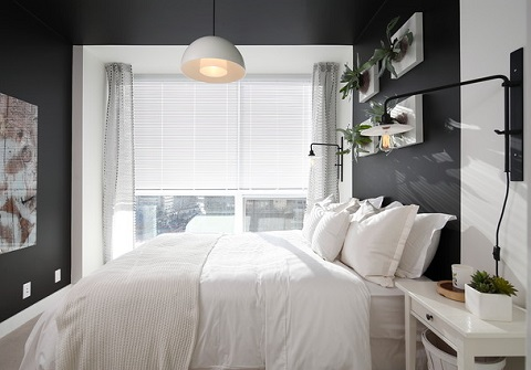 Replacing your bedside table lamp with a wall sconce, pendant, or swing arm light is a great way to declutter your nightstand (by i3 design group)