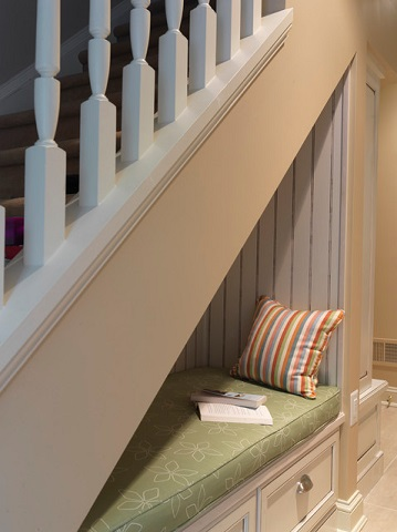 A reading nook under the stairs is the perfect place to get away with a good book, and can even host overnight guests in a pinch (by Case Design Remodeling Inc.)