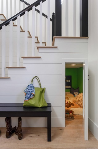 A small playroom underneath the stairs can be a fun getaway for small kids, and a child-sized door can conceal it nicely (by Von Fitz Design)