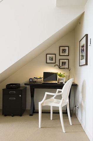 The bigger the staircase, the more space you'll have to build a small office underneath it, but even a relatively modest stairwell will have all the space you need for a basic home office setup (by Maria Killam)