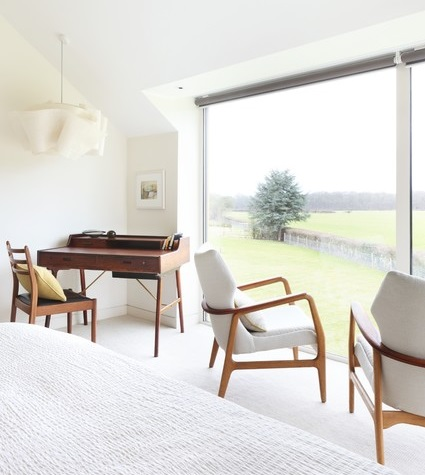 The simple, curvy wood arms and legs of mid century modern chairs stand out beautifully in a minimalist white on white room (via Houzz)