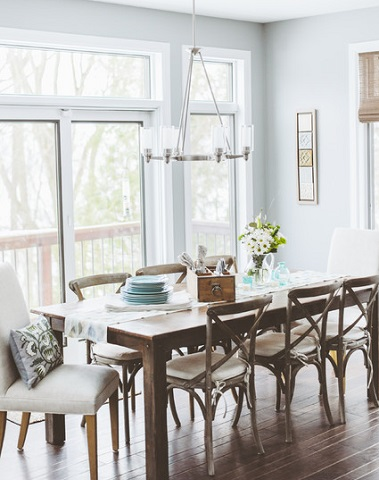 Adding upholstered chairs to a rustic dining table and antique wood chairs gives a cottage dining room a subtle hint of sophistication that can make a humble dining set feel more formal (by de[luxe] design studio)