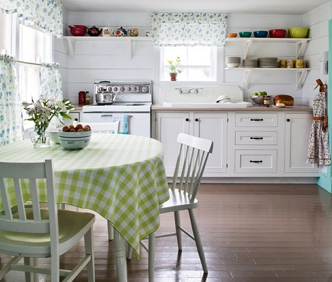 Quaint patterned fabrics, like these subtle floral window treatments or the gingham table cloth add charm and whimsy to a cottage style space (by CapeRace Cultural Adventures)