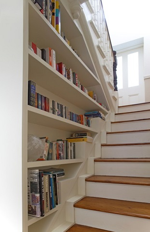 Recessed bookshelves can cover the entire wall of a staircase, converting a blank wall into charming shelf storage (by Optimise Design)