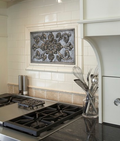 Set against a simple mosaic tile, a metallic decorative plaque can feel like an antique art piece (by Hendel Homes)