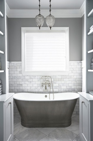 Marble subway tile has a more posh, sophisticated look than traditional white ceramic, and goes great with a trendy gray-on-gray bathroom decor (by Milestone Custom Homes)