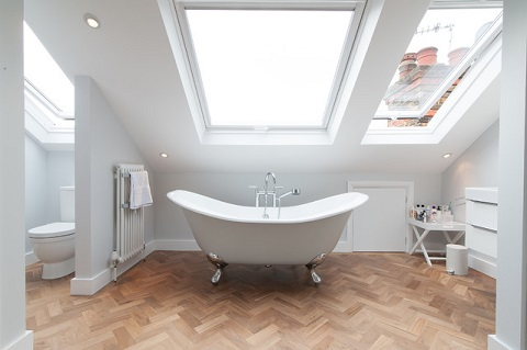 Placing a freestanding tub parallel to the lowest wall in an attic bathroom is the best way to keep the ceiling from feeling oppressive (by 50 Degrees North Architects, James Bailey)