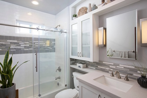 An image of a small gray bathroom with a low mosaic tile backsplash and matching tile accent in the shower