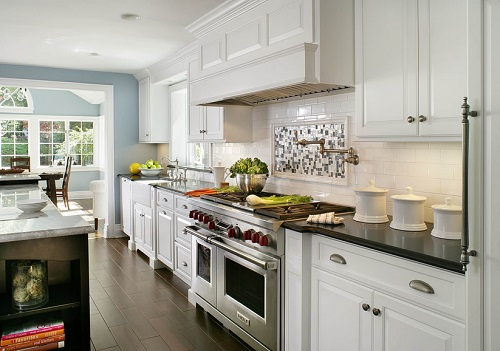 An image down the length of a kitchen. Above the range, the white subway tile is interrupted by a framed area of small black and white square tile