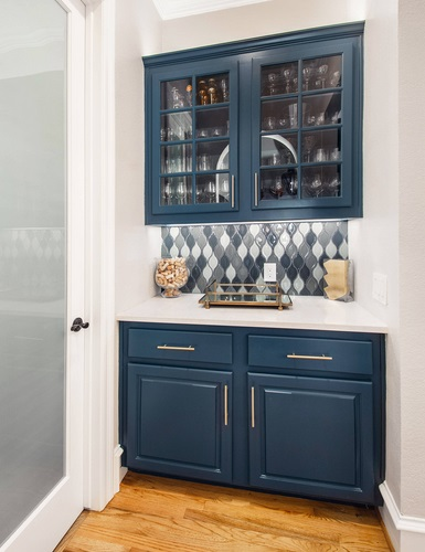 An image of a navy blue bar niche with mosaic tile on the wall between the upper and lower cabinets