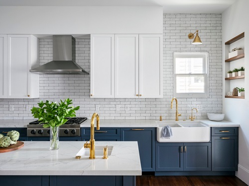 A transitional kitchen with blue lower cabinets and a ceiling-height marble tile backsplash