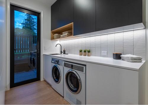 An image of a laundry room at dusk. Undercabinet lights illuminate the stacked white tile backsplash