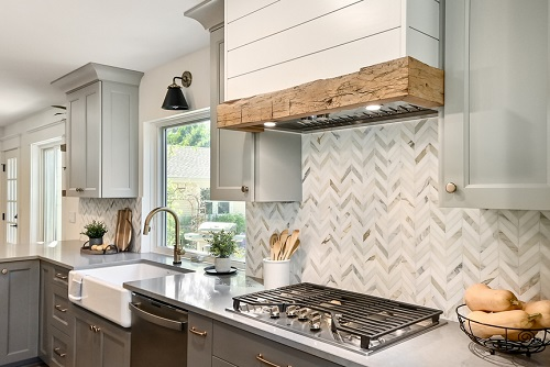 An image of a kitchen range with a marble tile backsplash done in a herringbone pattern