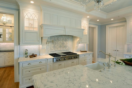 A classic white kitchen with cabinet lighting that emphasizes the herringbone tile backsplash and the ornately paned glass cabinet doors