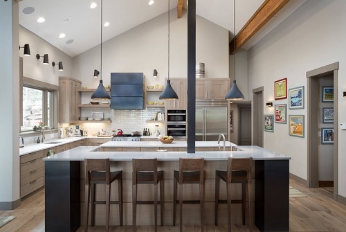 An image of a sleek modern wood kitchen with many, many layers of lights illuminating the space