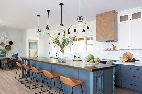 A blue and white kitchen with matte black hardware and lighting fixtures