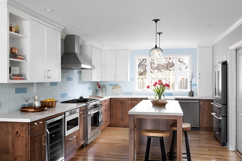 An image of a blue and white ktichen with wood cabinets. The edges of the ceiling are lined with recessed lights