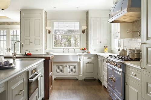 An image of a French country style kjitchen with matching sconces above the kitchen sink
