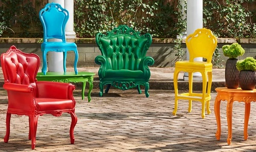 An image of four chairs and two tables lined up on a brick patio. Each one is a different solid, bold color