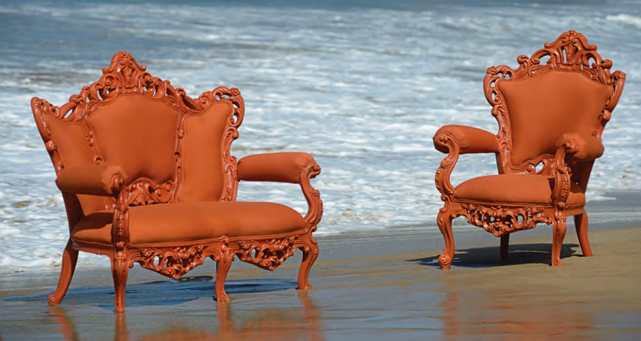 An image of a bright oragne, baroque-styled loveseat and armchair sitting in on the beach right at the tide line as waves come in