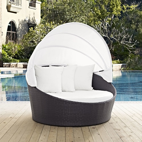 An image of a petite outdoor bed with white cushions and a white canopy, linking to a product page for the item
