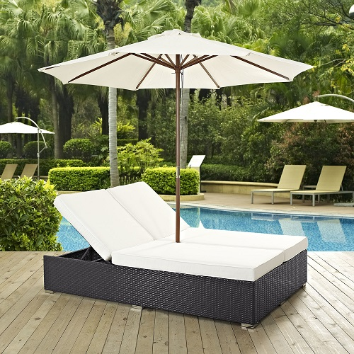 An image of a double lounge style outdoor bed with white cushions and a white umbrella, linking to a product page selling this item