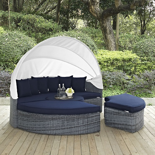 An image of a four-piece outdoor daybed with a white canopy and navy cushions, linking to a product page selling this item.
