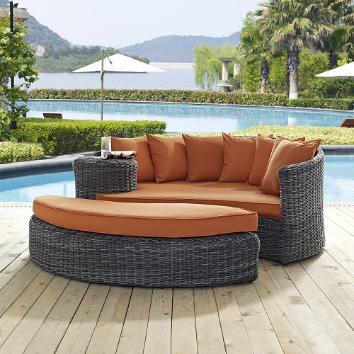 An image of a two-piece outdoor bed with a gray synthetic wicker body and orange cushions, linking to a page selling this item