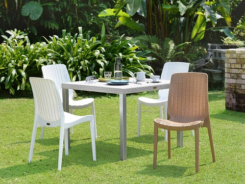 An image of a set of four stackable rattan dining chairs around a matching table, linking to a product page for the chair set
