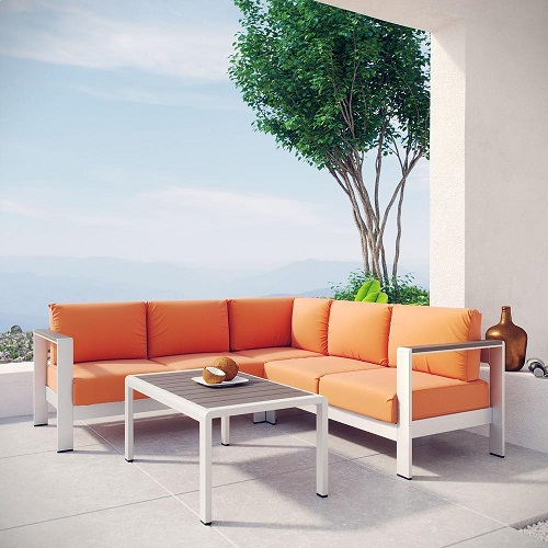 An image of an aluminum outdoor sectional set with orange cushions and a matching table, linking to the item's product page