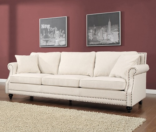 An image of an off-white linen sofa with nailhead tufting and bun feet