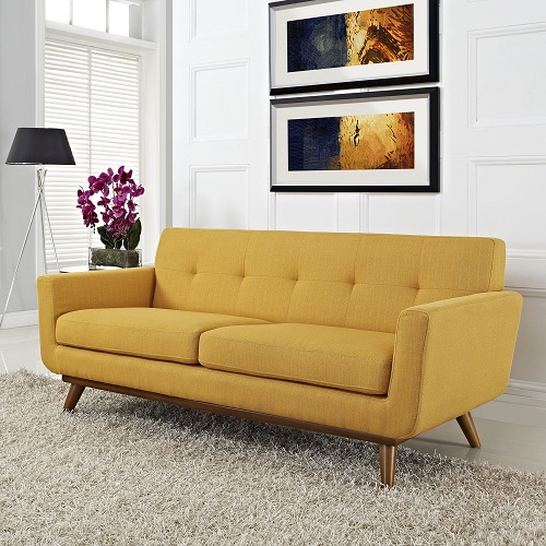A cheery mustard yellow sofa with midcentury style walnut legs and simple button tufting