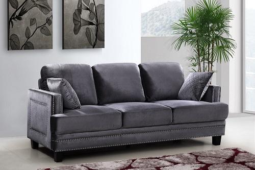 An image of a medium-gray velvet sofa, with extensive nailhead detailing, plum cushions, and a stout, rectangular design