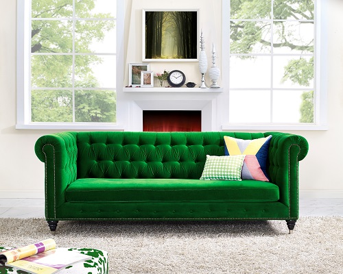An image of a bright emerald green sofa that features antique detailing, but has a distinctive contemporary feel