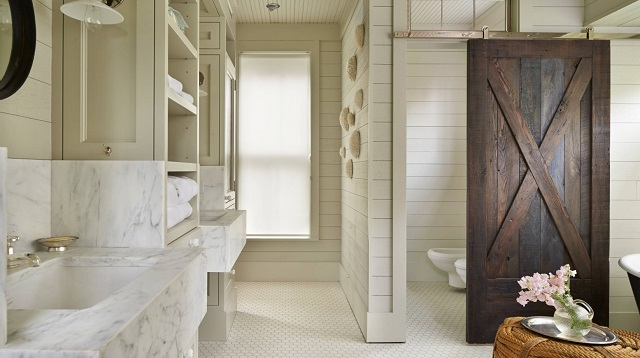 Barn doors slide out of the way, which gives them the unique ability to keep a large master bathroom feeling open while also providing added privacy (by Hoedemaker Pfeiffer)
