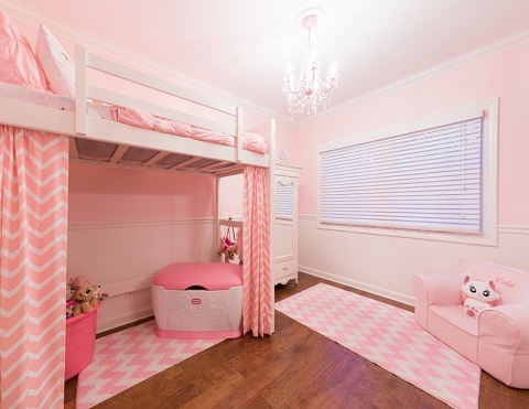 A bubblegum pink bedroom with a lofted bed and cute, kid-friendly chairs