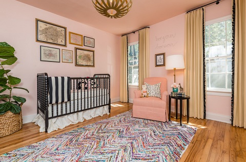 An image of a pink bedroom with a colorful rug, pale yellow curtains, and bold black furniture and hardware