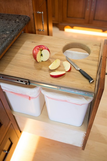 Concealed trash cans require sacrificing a little cabinet space, but can really streamline your workflow when you're actually using your kitchen (by Dynamic Woodworking)