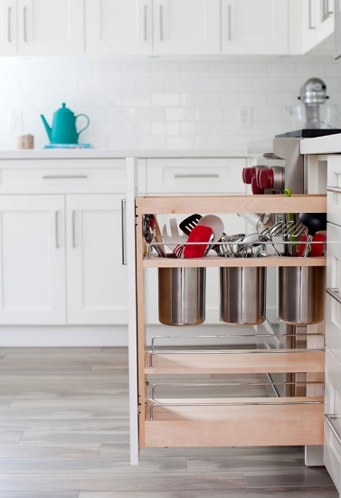 Combining pull-out shelves with utensil storage is a great way to get messy, odd-shaped utensils off your counters, out of your drawers, and finally organized and accessible (by Ritchie Construction Ltd)