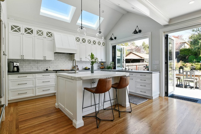 The windows and walls of this kitchen all fold out of the way, completely opening the greatroom to the outdoor kitchen and dining area beyond (by Dickinson Cabinetry)