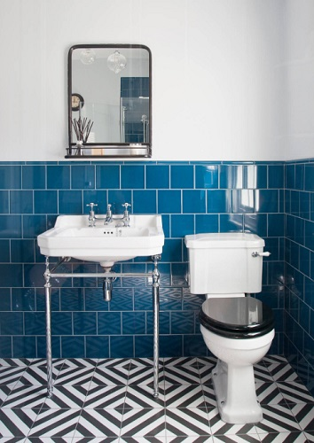 Using tile instead of traditional wainscoting is not only a great way to add color and patterning to your bathroom, but also makes your walls more water resistant and easier to clean (by The Brighton Bathroom Company)