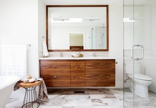 Installing a warm-toned wood bathroom vanity can totally transform a white bathroom (by RG Design Studio Inc.)