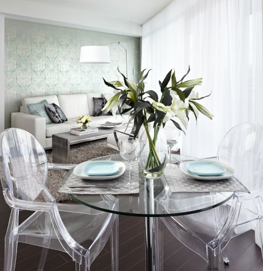 Pairing clear acrylic chairs with a glass topped table is a great way to squeeze a dining area into a small space without making it feel overcrowded (by Lisa Petrole)