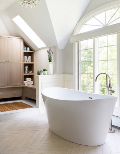 A photo of a modern freestanding tub and filler in front of an arched window