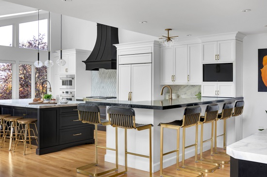 A photo of a black and white kitchen with two islands, one in a conventional spot near the range, the other featuring taller bar seating in an L-shape around the kitchen sink area