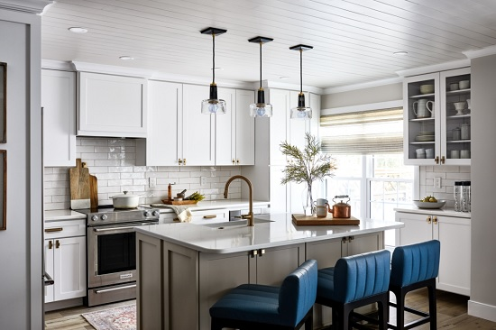 A photo of a cool gray kitchen cheered up with bright blue chairs, gold hardware, and a simple runner to soften the hard floors